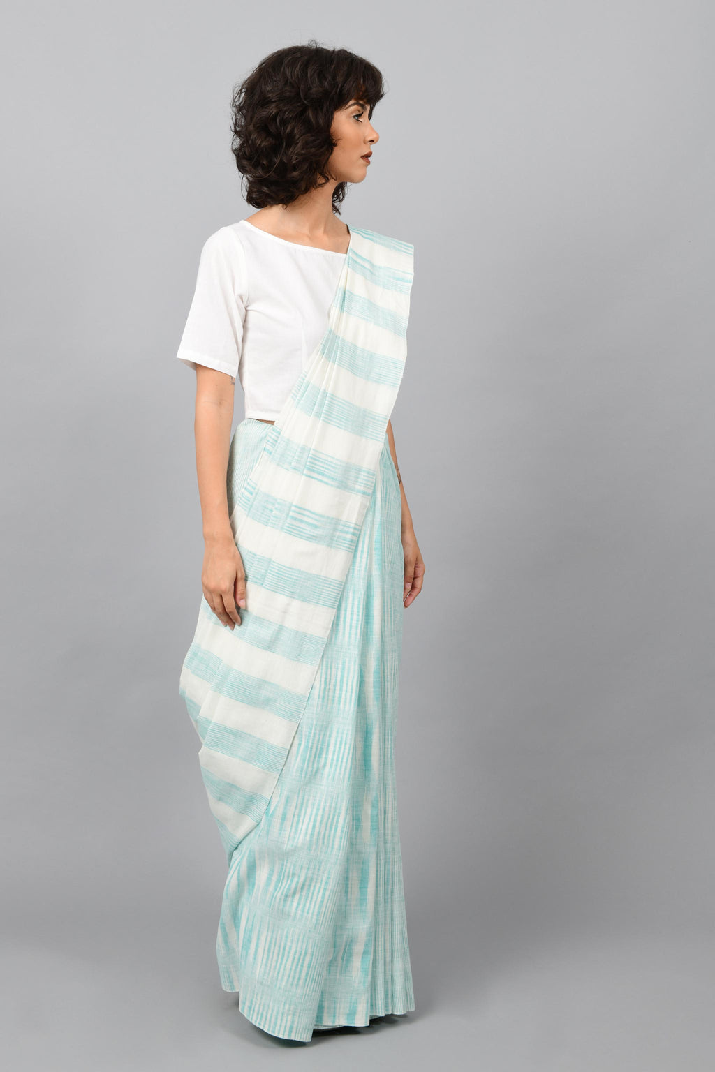 Side pose of a female womenswear fashion model draped in a aquamarine blue & white space dyed homespun and handwoven cotton sari by Cotton Rack.
