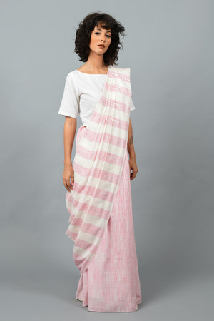 Side pose of a female womenswear fashion model draped in a pink & white space dyed homespun and handwoven cotton saree by Cotton Rack.