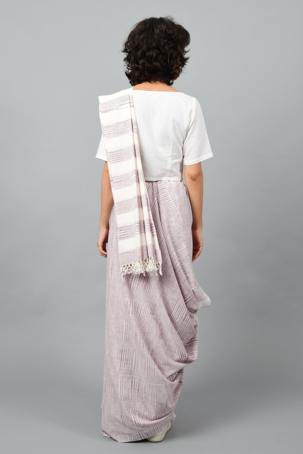 Back pose of a female womenswear fashion model draped in a purple & white space dyed homespun and handwoven cotton saree by Cotton Rack.
