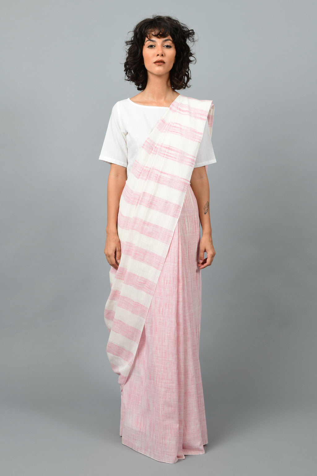 Front pose of a female womenswear fashion model draped in a pink & white space dyed homespun and handwoven cotton saree by Cotton Rack.