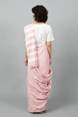 Back pose of a female womenswear fashion model draped in a red & white space dyed homespun and handwoven cotton sari by Cotton Rack.