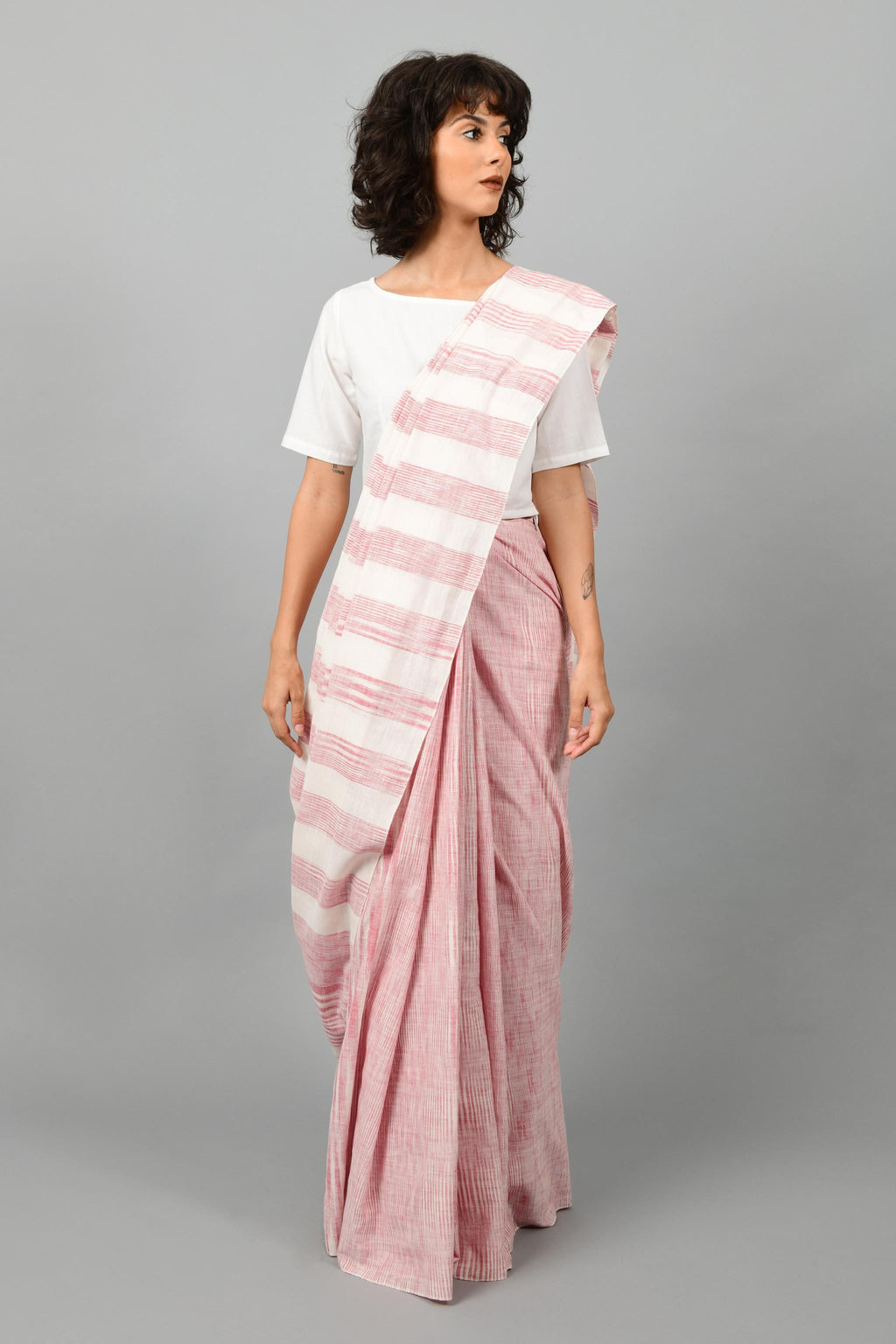 Front pose of a female womenswear fashion model draped in a red & white space dyed homespun and handwoven cotton sari by Cotton Rack.