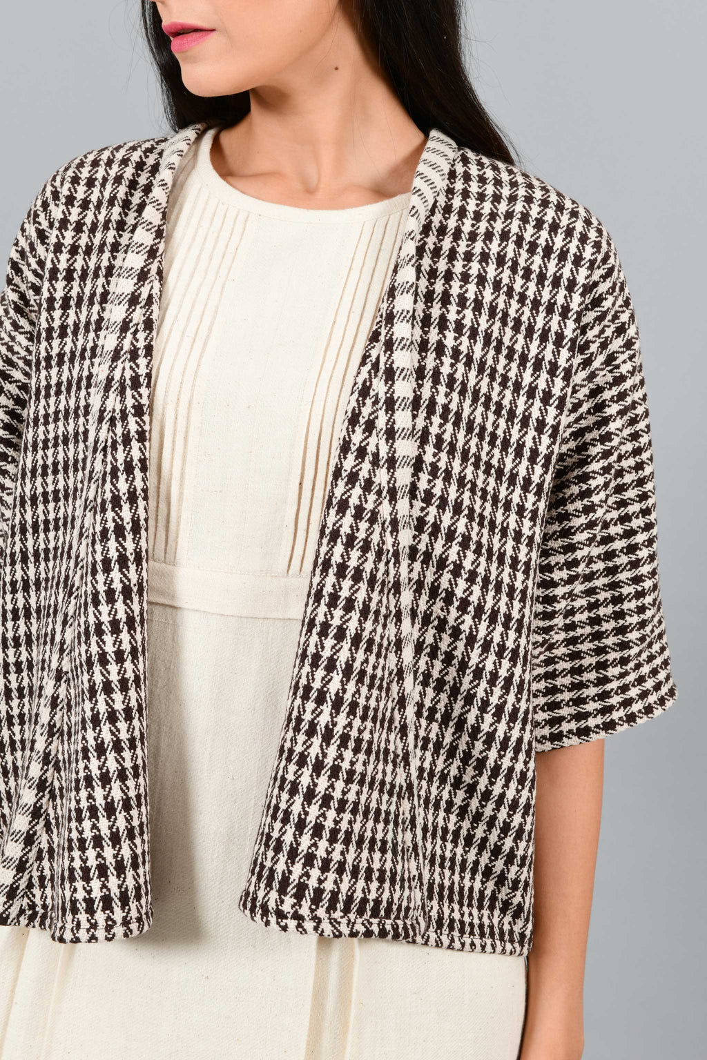 Front close up of an Indian Womenswear female model wearing Brown and off-white chequred handspun and handwoven free size shrug Jacket over an off-white cashmere cotton dress by Cotton Rack.