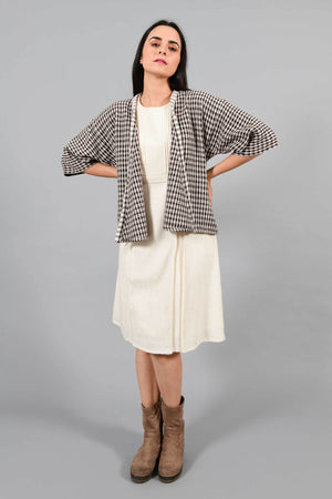Front pose of an Indian Womenswear female model with hands on waist wearing Brown and off-white chequred handspun and handwoven free size shrug Jacket over an off-white cashmere cotton dress by Cotton Rack.