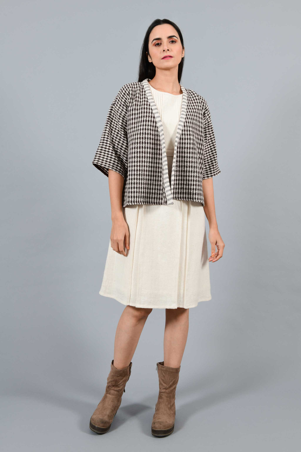Front pose of an Indian Womenswear female model wearing Brown and off-white chequred handspun and handwoven free size shrug Jacket over an off-white cashmere cotton dress by Cotton Rack.
