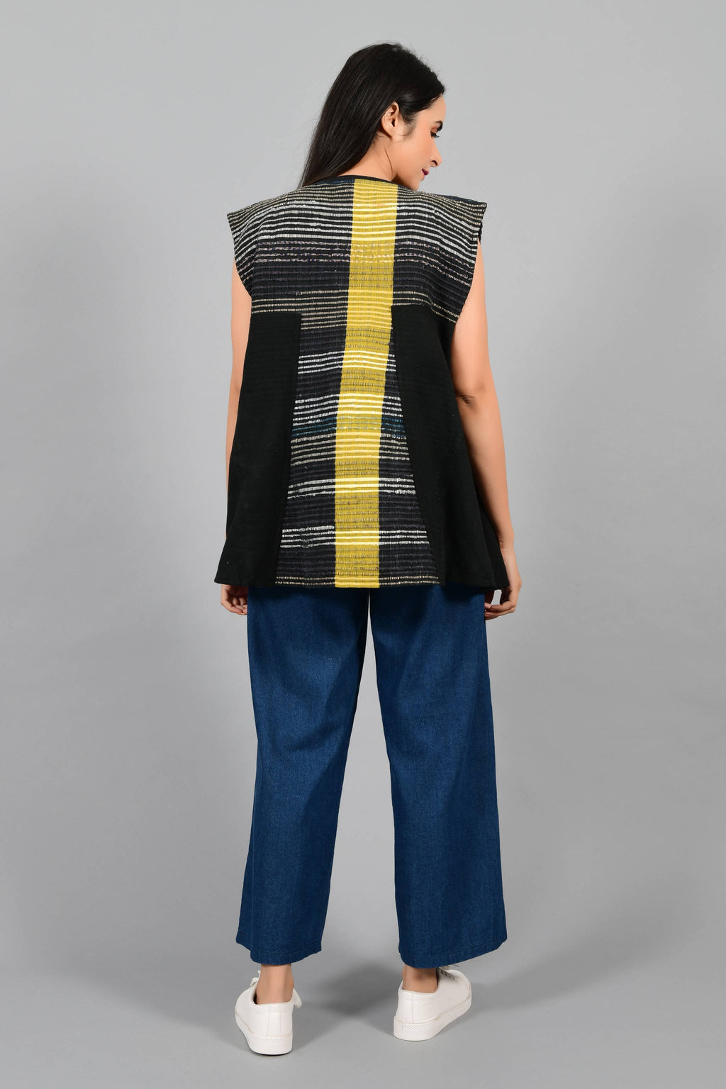 Back pose of an Indian Womenswear female model wearing black upcycled sleeveless jacket with a yellow stripe made with handspun and handwoven cotton by Cotton Rack.