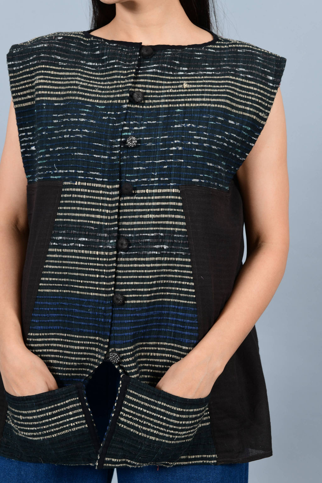 Front close up pose of an Indian Womenswear female model wearing black upcycled kimono inspired sleeveless jacket made with handspun and handwoven cotton by Cotton Rack.