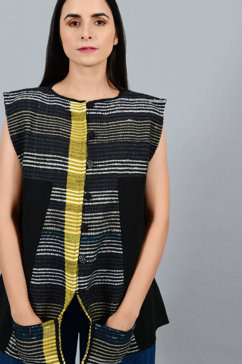 Close Up pose of an Indian Womenswear female model wearing black upcycled sleeveless jacket with a yellow stripe made with handspun and handwoven cotton by Cotton Rack.
