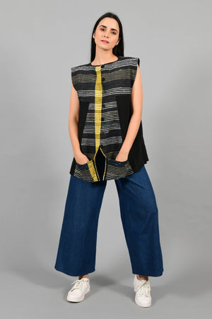 Front pose of an Indian Womenswear female model wearing black upcycled sleeveless jacket with a yellow stripe made with handspun and handwoven cotton by Cotton Rack.