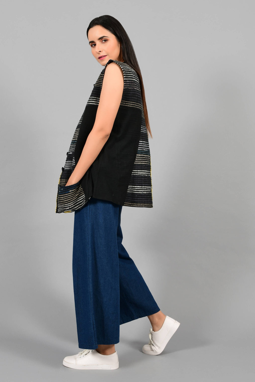 Side pose of an Indian Womenswear female model wearing black upcycled sleeveless jacket with a yellow stripe made with handspun and handwoven cotton by Cotton Rack.