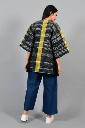 Back pose of an Indian Womenswear female model wearing black upcycled kimono inspired jacket with a yellow stripe made with handspun and handwoven cotton by Cotton Rack.