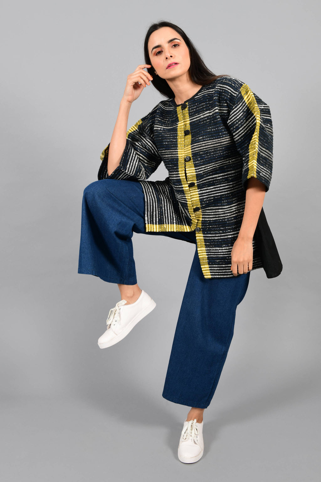 Front stylised pose of an Indian Womenswear female model wearing black upcycled kimono inspired jacket with a yellow stripe made with handspun and handwoven cotton by Cotton Rack.