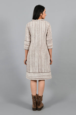 Back pose of an Indian Womenswear female model wearing brown handspun and handwoven cotton a-line dress by Cotton Rack.