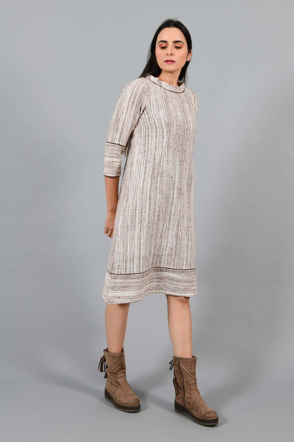 Side walking pose of an Indian Womenswear female model wearing brown handspun and handwoven cotton a-line dress by Cotton Rack.