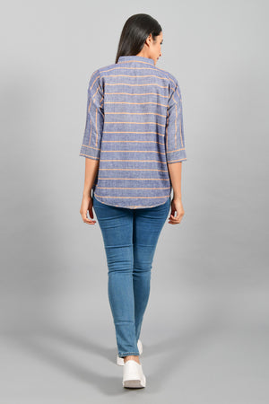 Back pose of an Indian female womenswear fashion model in a blue chambray with orange stripes handspun and handwoven khadi cotton free size top by Cotton Rack.