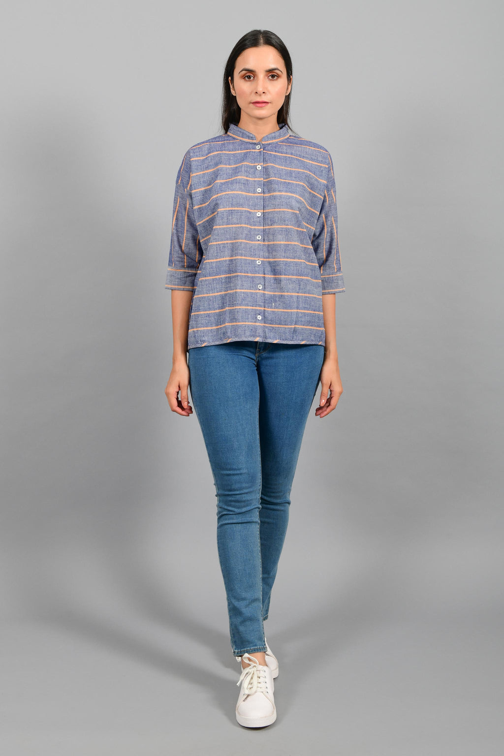 Front pose of an Indian female womenswear fashion model in a blue chambray with orange stripes handspun and handwoven khadi cotton free size top by Cotton Rack.