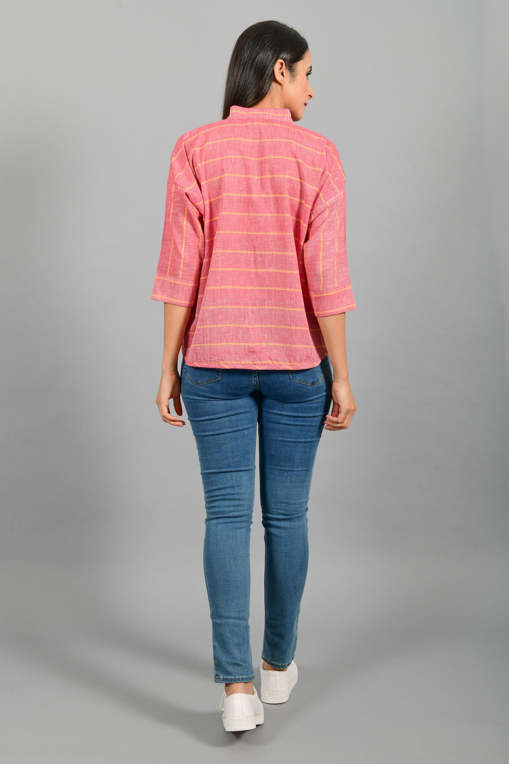 Back pose of an Indian female womenswear fashion model in a red chambray with orange stripes handspun and handwoven khadi cotton free size top by Cotton Rack.