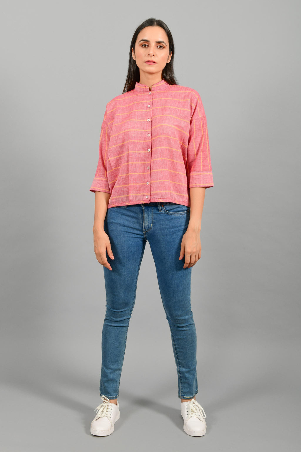 Front pose of an Indian female womenswear fashion model in a red chambray with orange stripes handspun and handwoven khadi cotton free size top by Cotton Rack.