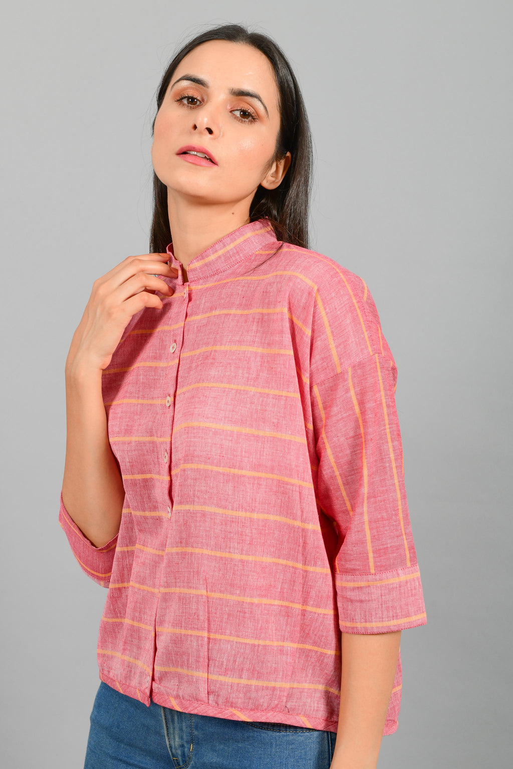Close Up portrait of an Indian female womenswear fashion model in a red chambray with orange stripes handspun and handwoven khadi cotton free size top by Cotton Rack.