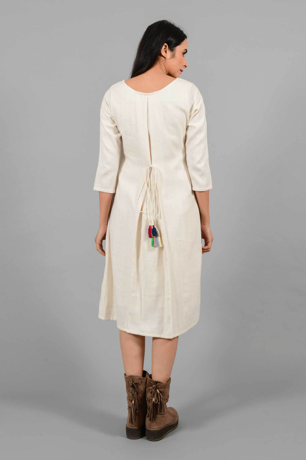 Back pose of an Indian female womenswear fashion model in an off-white Cashmere Cotton A-line Dress with box pleat on the back made using handspun and handwoven khadi cotton by Cotton Rack.
