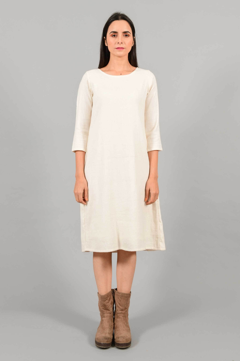 Front pose of an Indian female womenswear fashion model in an off-white Cashmere Cotton A-line Dress with box pleat on the back made using handspun and handwoven khadi cotton by Cotton Rack.