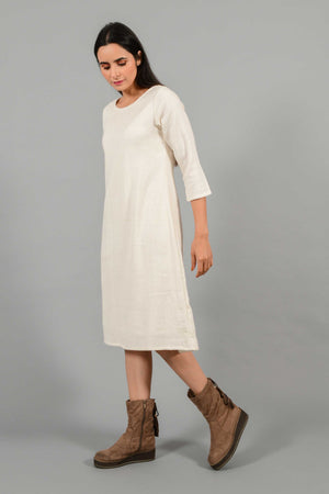 Side pose of an Indian female womenswear fashion model in an off-white Cashmere Cotton A-line Dress with box pleat on the back made using handspun and handwoven khadi cotton by Cotton Rack.