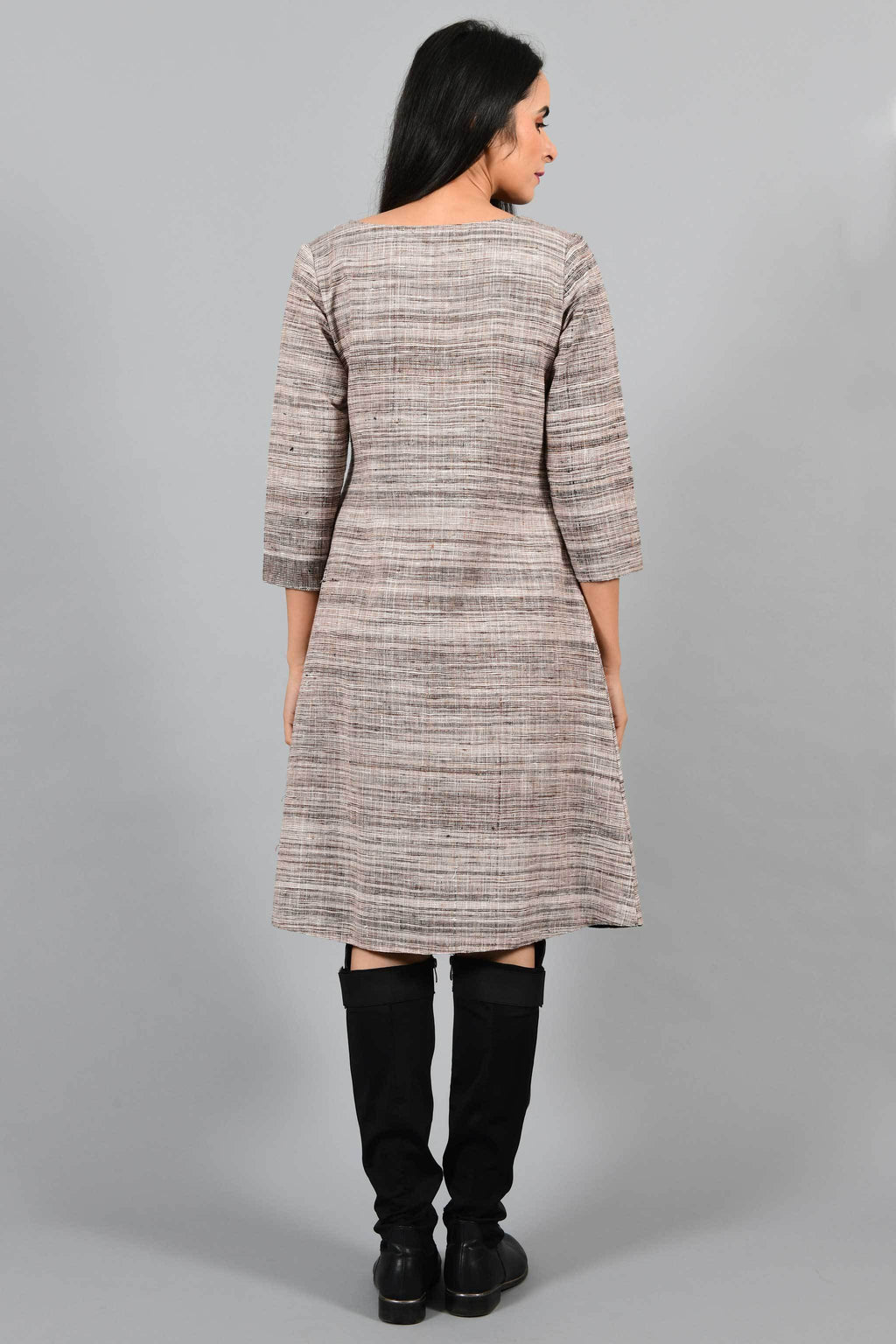 Back pose of an Indian Womenswear female model wearing brown-black textured handspun and handwoven cotton angrakha dress by Cotton Rack with black boots.