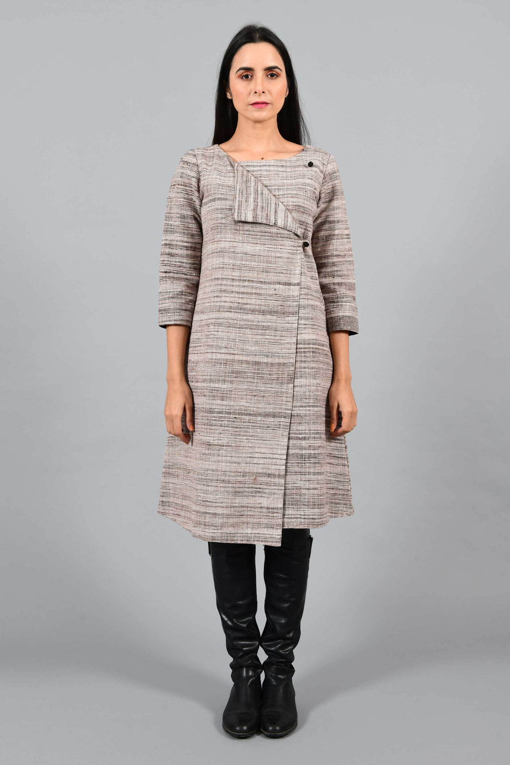 Front pose of an Indian Womenswear female model wearing brown-black textured handspun and handwoven cotton angrakha dress by Cotton Rack with black boots.