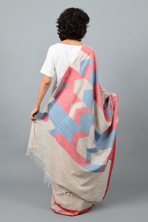 Back pose of a female womenswear fashion model draped in a Beige red & blue Jamdani space dyed homespun and handwoven 100s cotton sari by Cotton Rack.