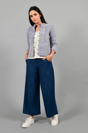 Front pose of an Indian Womenswear female model wearing Indigo Blue Gandhi Charkha spun and handwoven khadi buttoned mandarin collar Jacket over an off-white spaghetti and indigo palazzos by Cotton Rack.