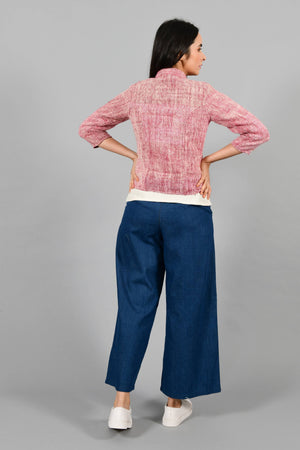 Back pose of an Indian Womenswear female model wearing plum red Gandhi Charkha spun and handwoven khadi buttoned mandarin collar Jacket over an off-white spaghetti and indigo palazzos by Cotton Rack.