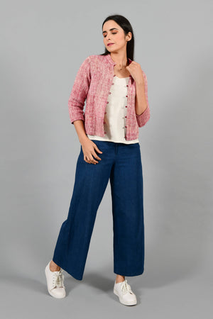 Stylised front pose of an Indian Womenswear female model wearing plum red Gandhi Charkha spun and handwoven khadi buttoned mandarin collar Jacket over an off-white spaghetti and indigo palazzos by Cotton Rack.