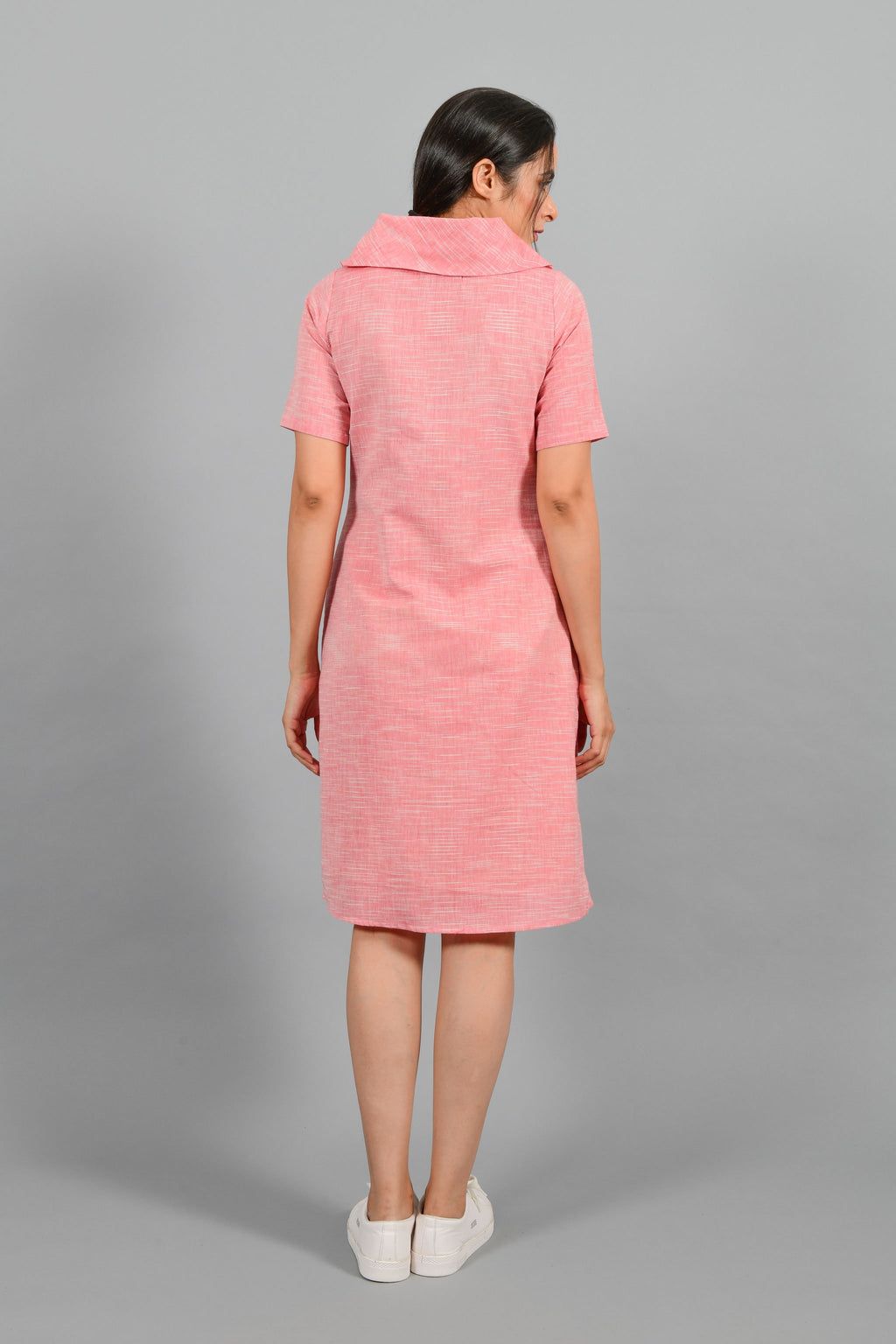 Back pose of an Indian female womenswear fashion model in a Pink and White space dyed cowl neck, elbow sleeve handspun and handwoven khadi cotton dress by Cotton Rack.