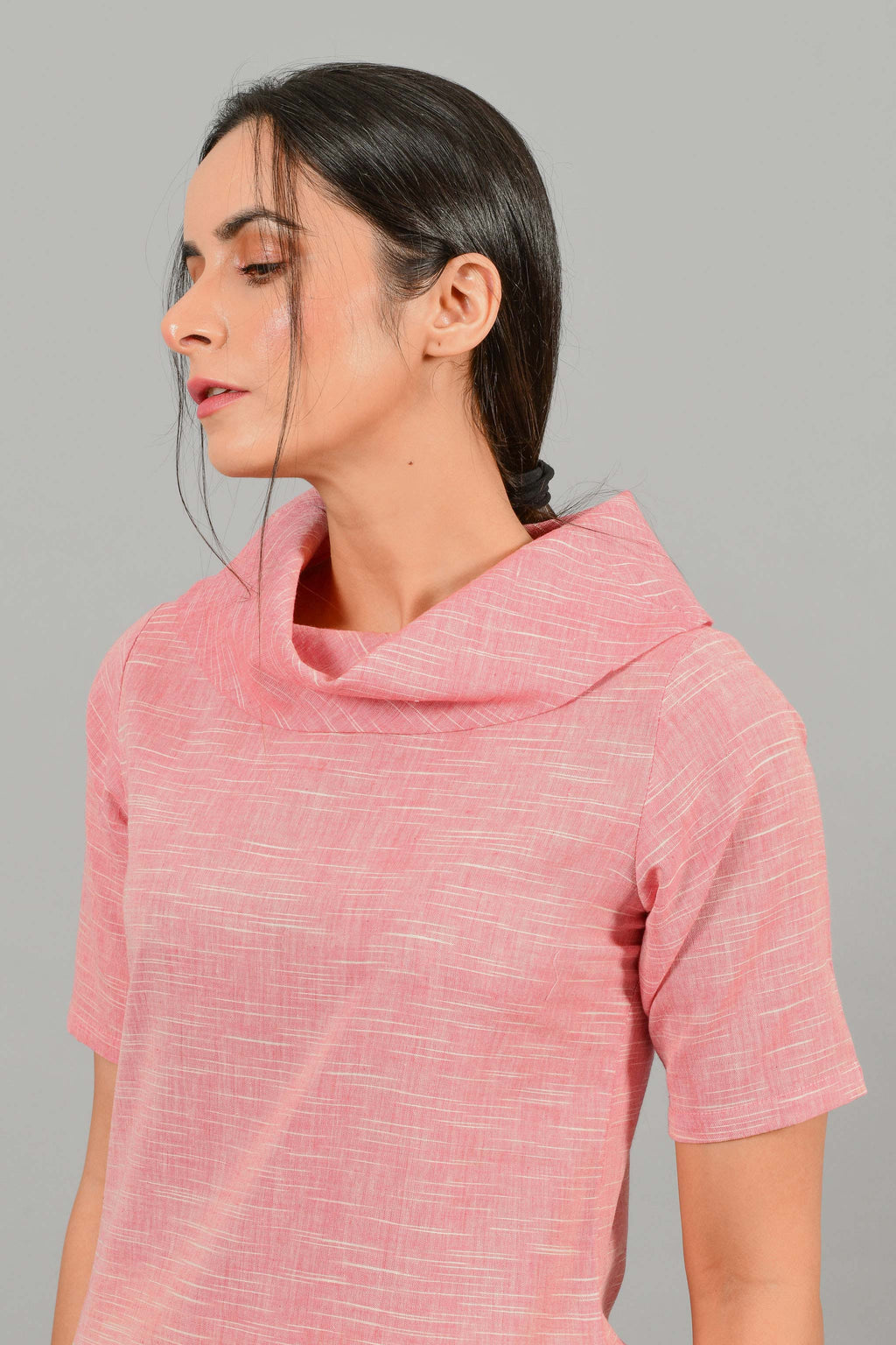 Front portrait pose of an Indian female womenswear fashion model in a Pink and White space dyed cowl neck, elbow sleeve handspun and handwoven khadi cotton dress by Cotton Rack.