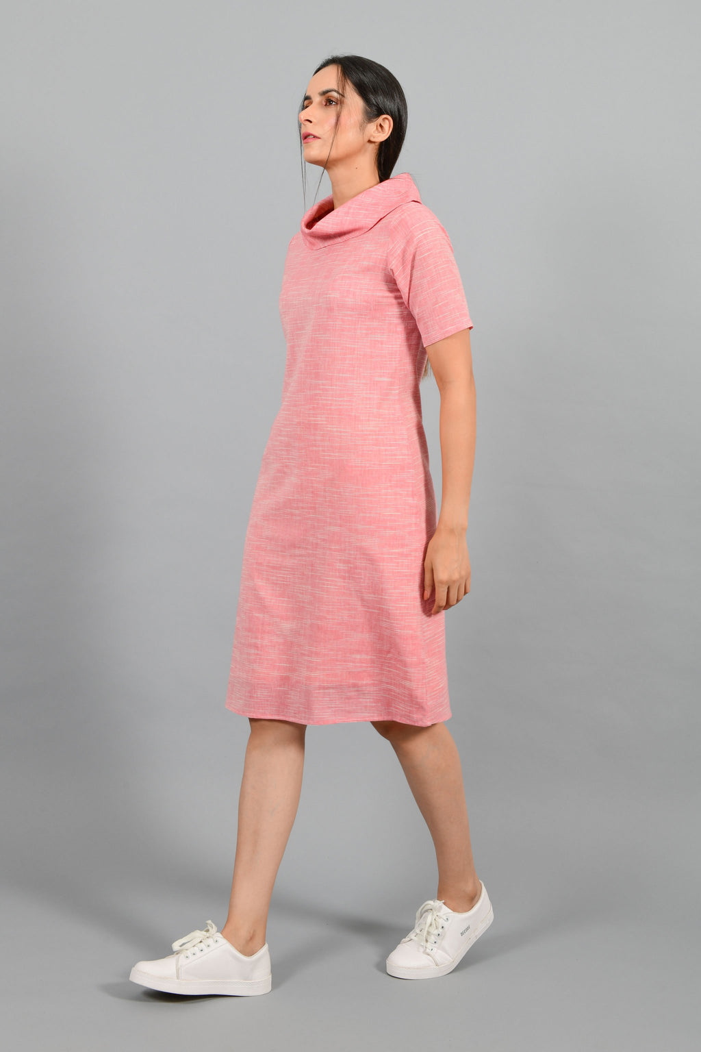 Side pose of an Indian female womenswear fashion model in a Pink and White space dyed cowl neck, elbow sleeve handspun and handwoven khadi cotton dress by Cotton Rack.