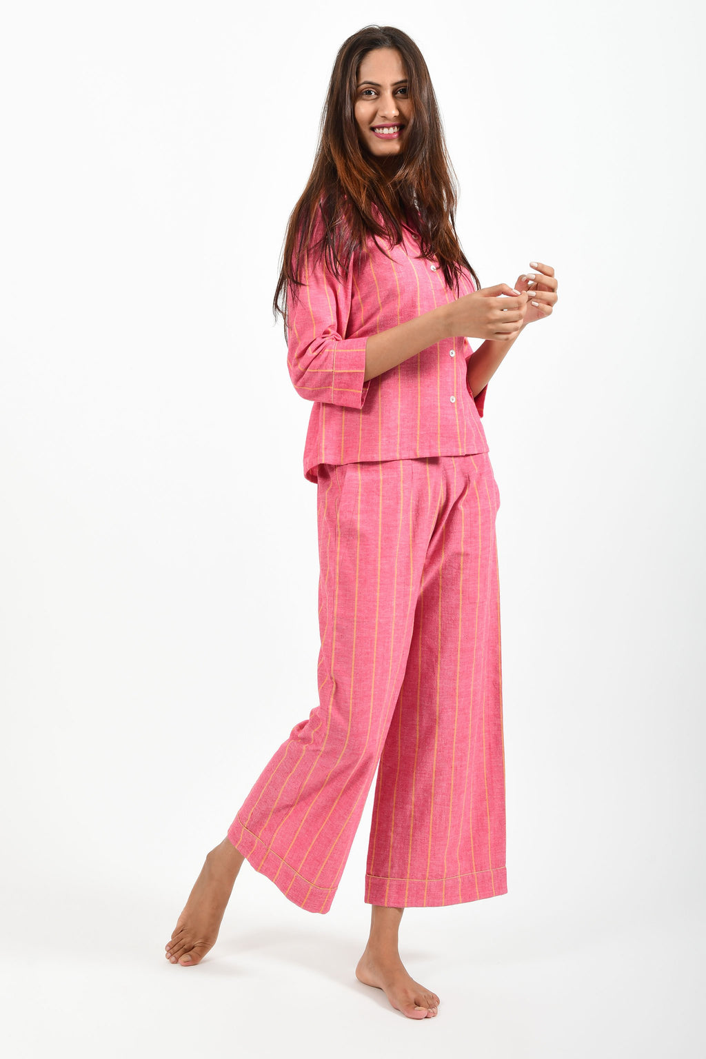 Creative pose of an Indian female womenswear fashion model in azo-free dyed handspun and handwoven khadi cotton nightwear pyjama & shirt with red base and orange stripes by Cotton Rack.