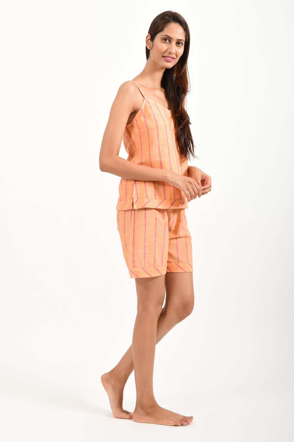 Side pose of an Indian female womenswear fashion model in azo-free dyed orange chambray (with red stripes) handspun and handwoven khadi cotton spaghetti top and boxers by Cotton Rack.