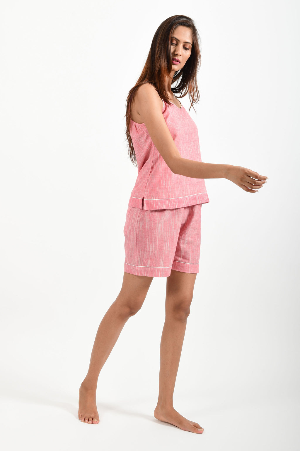 Side pose of an Indian female womenswear fashion model in azo-free space dyed pink handspun and handwoven khadi cotton spaghetti top and boxers by Cotton Rack.