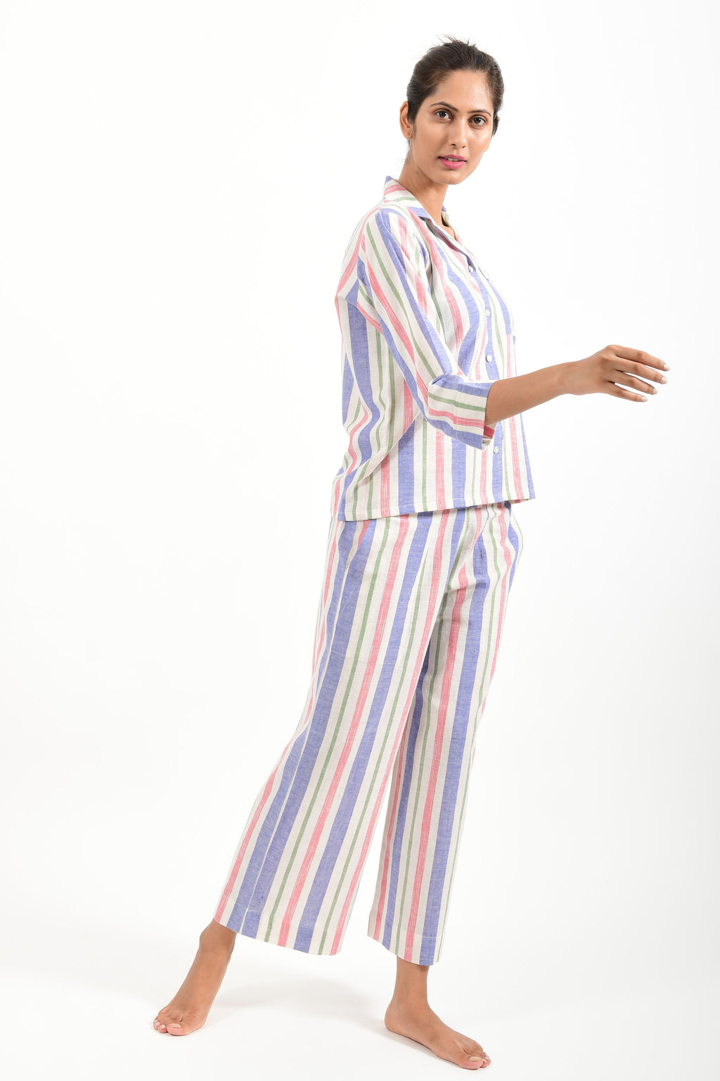 Side pose of an Indian female womenswear fashion model in a candy colored striped azo-free dyed handspun and handwoven khadi cotton nightwear pyjama & shirt by Cotton Rack.