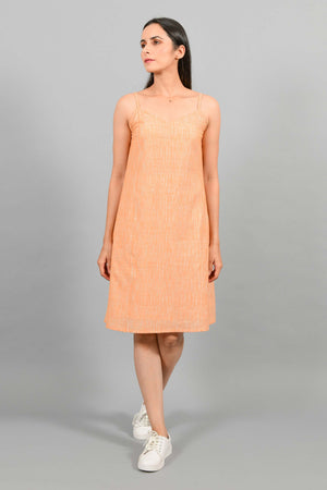 Front pose of an Indian female womenswear fashion model in an orange space dyed handspun and handwoven khadi cotton spaghetti dress by Cotton Rack.