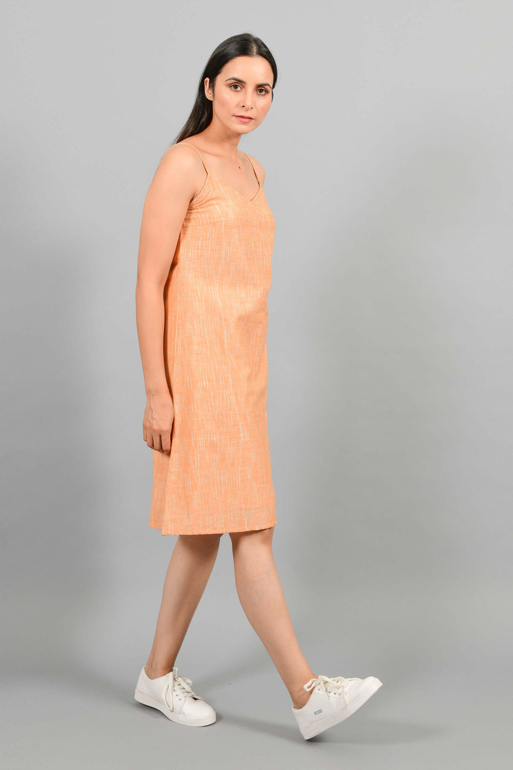 Stylised side pose of an Indian female womenswear fashion model in an orange space dyed handspun and handwoven khadi cotton spaghetti dress by Cotton Rack.