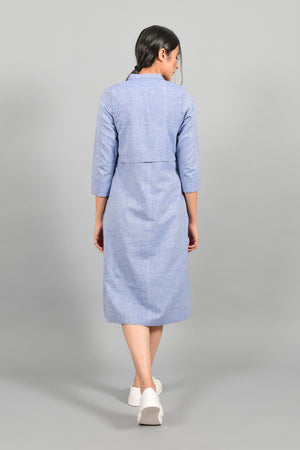 Back pose of an Indian female womenswear fashion model in a blue chambray handspun and handwoven khadi cotton shirt dress by Cotton Rack.