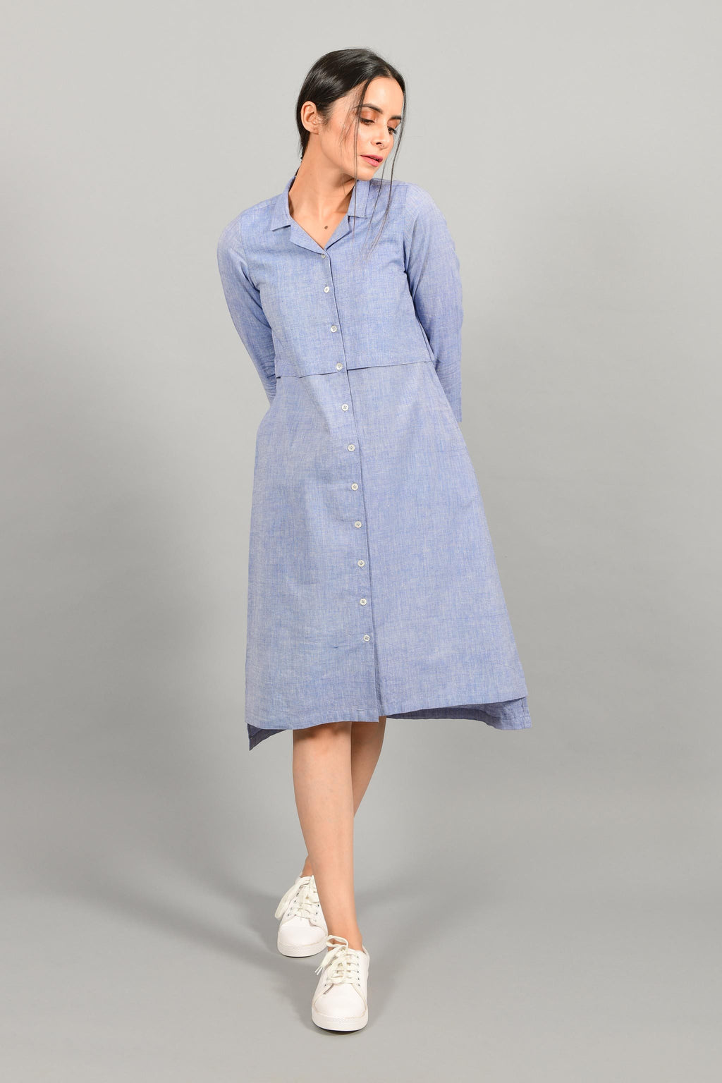 Front stylised pose of an Indian female womenswear fashion model in a blue chambray handspun and handwoven khadi cotton shirt dress by Cotton Rack.