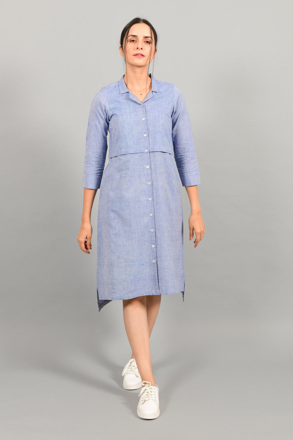 Front pose of an Indian female womenswear fashion model in a blue chambray handspun and handwoven khadi cotton shirt dress by Cotton Rack.