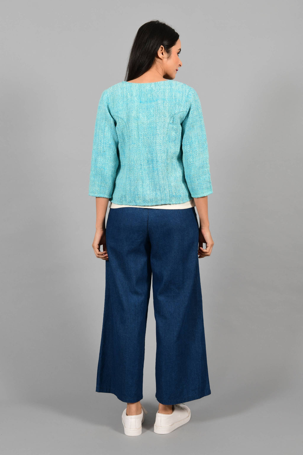 Back pose of an Indian Womenswear female model wearing aqua blue and Gandhi Charkha spun and handwoven khadi Jacket over an off-white spaghetti and indigo palazzos by Cotton Rack.