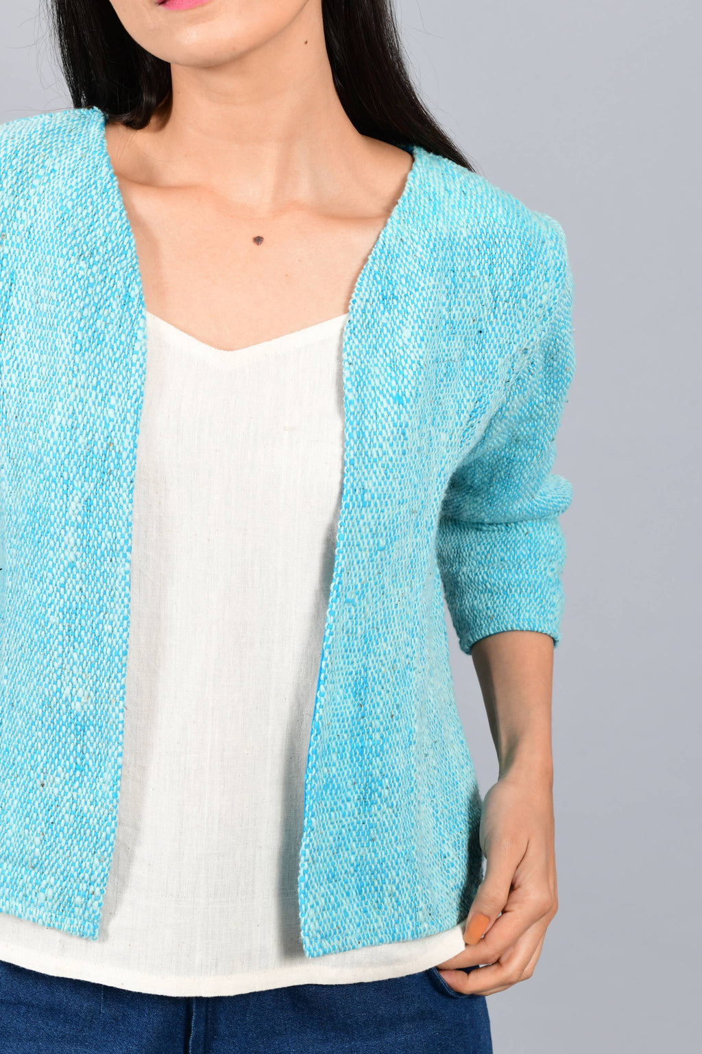 Front close up of an Indian Womenswear female model wearing aqua blue and Gandhi Charkha spun and handwoven khadi Jacket over an off-white spaghetti and indigo palazzos by Cotton Rack.