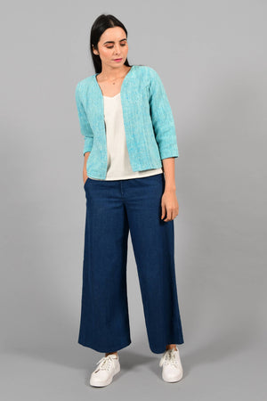 Front pose of an Indian Womenswear female model wearing aqua blue and Gandhi Charkha spun and handwoven khadi Jacket over an off-white spaghetti and indigo palazzos by Cotton Rack.
