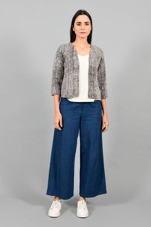 Front pose of an Indian Womenswear female model wearing black and Gandhi Charkha spun and handwoven khadi Jacket over an off-white spaghetti and indigo palazzos by Cotton Rack.