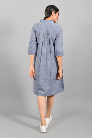Back pose of an Indian female womenswear fashion model in a blue chambray handspun and handwoven khadi cotton dress-kurta by Cotton Rack.