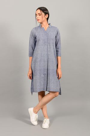 Front pose of an Indian female womenswear fashion model in a blue chambray handspun and handwoven khadi cotton dress-kurta by Cotton Rack.